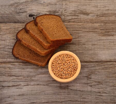 Wheat grains in a wooden bowl and bread.