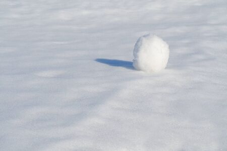 Big snow ball on white snowy field.