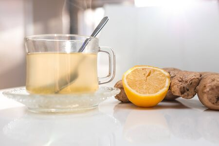 Glass cup of hot ginger tea with ginger rhizome (root) sliced and lemon, isolated on white background.
