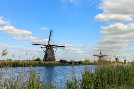 Dutch old windmills, river en blue cloudy sky on landscape, Kinderdijk in South Holland, Netherlands 版權商用圖片