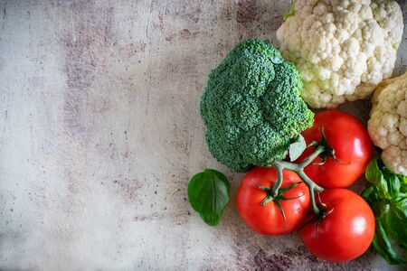 Fresh vegetables: juicy tomatoes on a branch, broccoli head, cauliflower inflorescences and fragrant Basil on a beautiful background