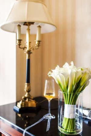 White Callas: Ramo de la boda con las calas blancas en el vaso sobre la mesa
