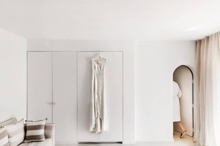 Wedding dress hanging on the wall in the white room. The bride in the dressing gown comes out and the rooms. Stockfoto