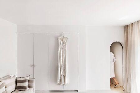 Vestido de casamento que pendura na parede na sala branca. A noiva do roupão sai e os quartos.