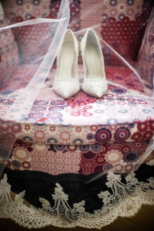 Wedding shoes and veil on the vintage chair. Stock Photo
