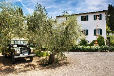 Weddign dress hanging in the window, beautiful bride and old car. Italian villa. Villa Bordoni.