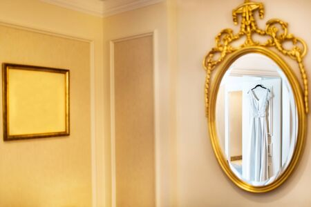 Elegant wedding dress hanging on the door and reflecting in the mirror.