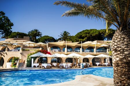 Swimming pool at hotel, palm, tables and other trees. Stok Fotoğraf