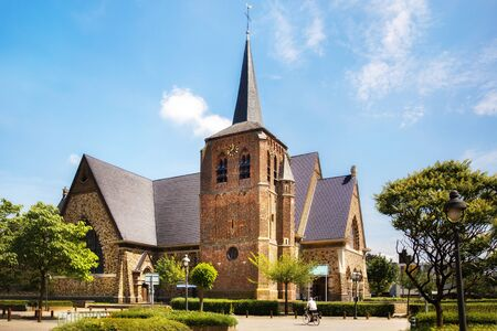Catholic Church Sint-Martinuskerk in Houthalen-Helchteren, Belgium. Man on a bicycle.