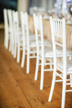 A row of white chairs next to the wedding tables.