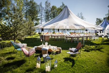 Wedding tent with large balls. Tables sets for wedding or another catered event dinner. Фото со стока