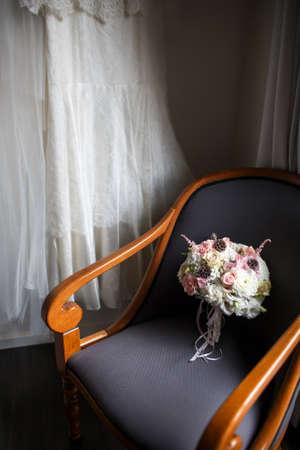 Wedding bouquet on a wooden chair. Wedding dress. Stock Photo