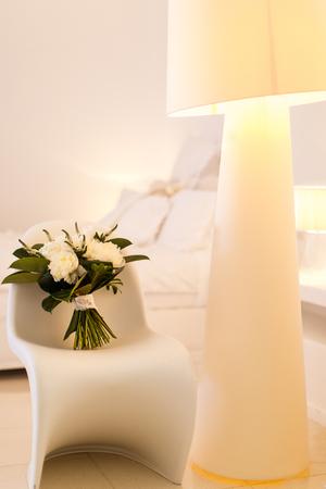 Beautiful wedding bouquet on a chair. Beige lamp.