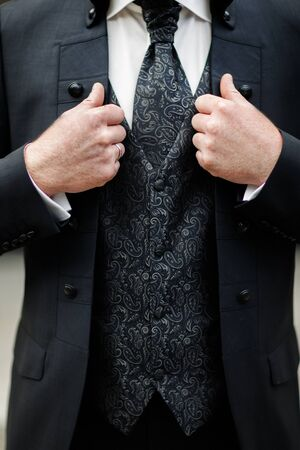 Close-up of elegance male hands wearing modern black suit.