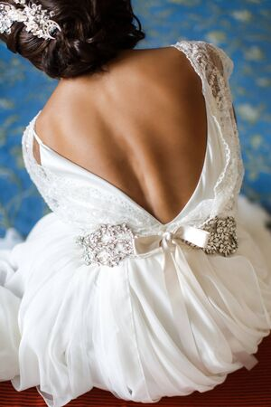 The back of a beautiful bride. The bride sits on a chair.