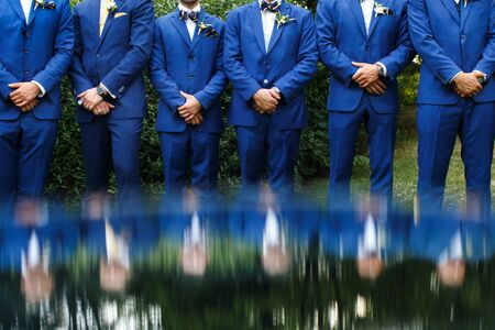 The groomsman in blue suits stand in a row.