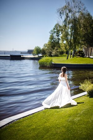 Bride in a beautiful dress walking in the summer in the park. Stock fotó