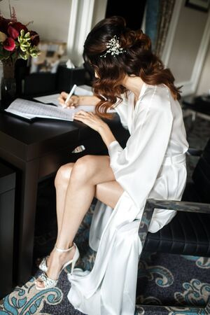 Bride in the lace robe is writing a vow for the wedding. Stock Photo