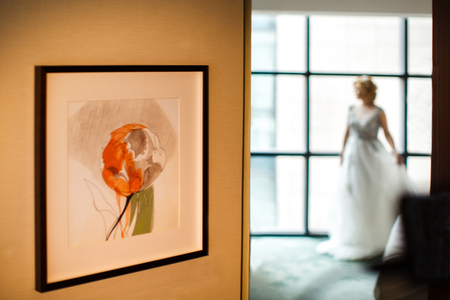 Beautiful bride stands near the window and the picture. Stock fotó
