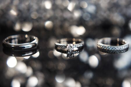 Three wedding rings on the reflecting surface with highlights. Stock fotó
