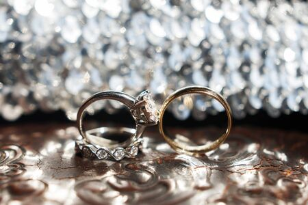 Three wedding rings on the reflecting surface with highlights. Stock Photo