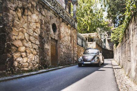 Quinta da Regaleira의 돌담과 갈색 차. 신트라, 포르투갈.