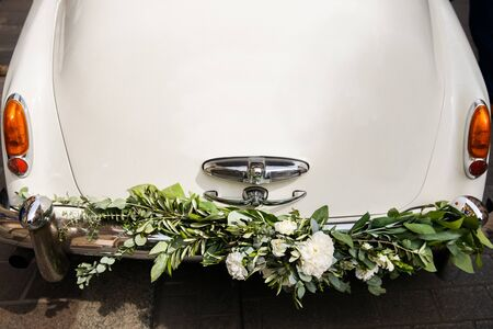 Vintage wedding car decorated with flowers, close up.