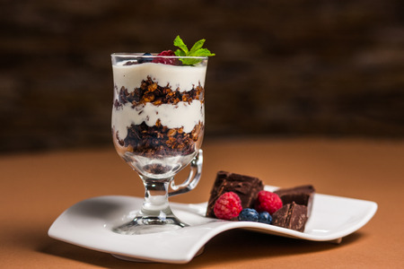 Yogurt with cream, chocolate, strawberry and muesli served in glass