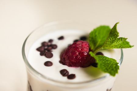 Yogurt with cream, raspberries served in glass on white background Stock fotó