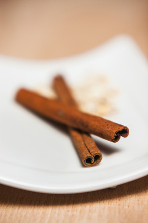 Bowl of cinnamon on a plate on wooden table