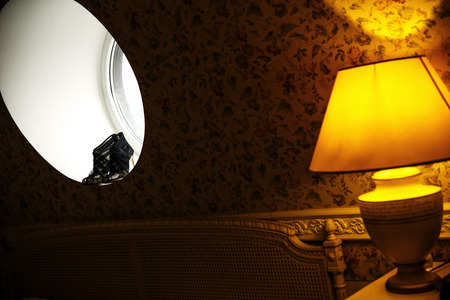 Black wedding shoes on the round window and vintage lamp