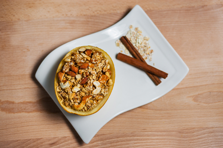 Homemade granola in a plate of melon on wooden table Stock fotó