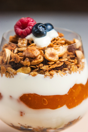 Yogurt with cream, strawberry and muesli served in glass on white table