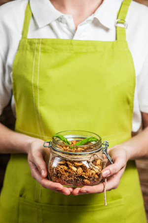 Homemade granola in glass jar in the hands of a girl