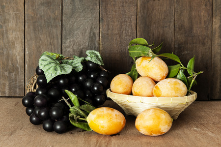 Marian plum or maprang on wood background,grapes