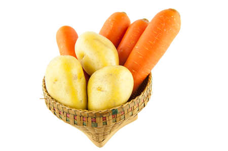 Potatoes and carrots in a basket on a white background.