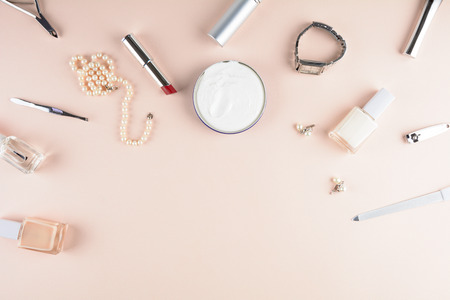 Skin care concept. Femenine accessories, nail polish, hand cream on puffy background. Flat lay. Top view