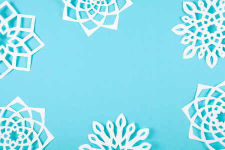 Paper snowflakes on blue background. Top view. Christmas decoration. Toned