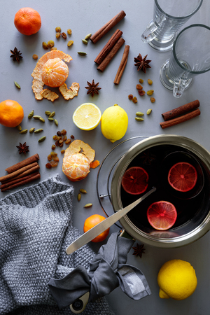 Mulled wine in aluminum casserole on gray wooden table. Christmas or winter warming drink. Ingredients: wine, lemon, cinnamon sticks, anise, cardamon, raisin. Top view. Flat lay