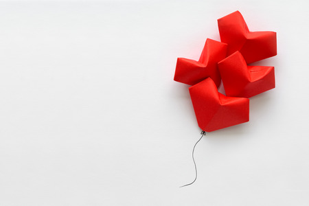 Valentines day card. Red paper heart shape balloons on thread. Origami and minimalist concept Stock Photo