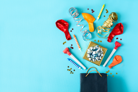 Collection of colorful birthday party objects in a gift box on blue paper background. Holiday celebration concept. Copy space. Flat lay