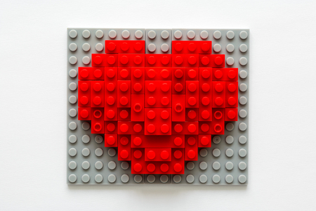 Red heart made from building blocks on gray background. Valentines day celebration and minimalist concept. Imagens