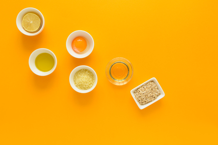 Fresh ingredients for homemade effective acne remedies on yellow background. Honey, sea salt, egg yolk, olive oil, oat, lemon and aloe. Flat lay. Copy space