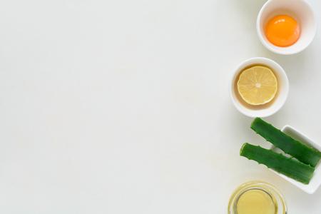 Fresh ingredients for homemade effective acne remedies on white background. Honey, sea salt, egg yolk, olive oil, oat, lemon and aloe. Flat lay. Copy space Imagens
