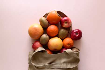 Cotton bag with differnt fruits on pink background. Ecology pack for free plastic shopping. Top view. Flat lay