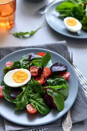 Salad mix with spinach, arugula,beet leaves, tomatoes and eggs on gray wooden background. Vegetarian food concept. Selective focus.