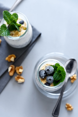 Chia seed pudding with granola, blueberry, walnut and honey decorated mint leaves on gray backgraund. Selective focus. Healthy eating or vegetarian food concept