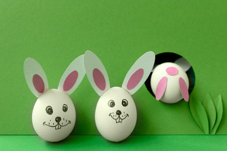 Easter bunny made from eggs and paper ears jump in hole on green pastel background. Creative idea. Art food concept.