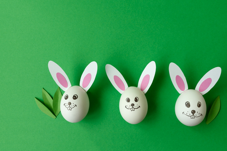 Easter bunny made from eggs and paper ears on green pastel background. Creative idea. Art food concept. Flat lay