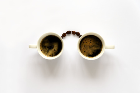 Homan face with glasses from two espresso cups and coffee beans. Coffee art or creative concept. Top view Imagens